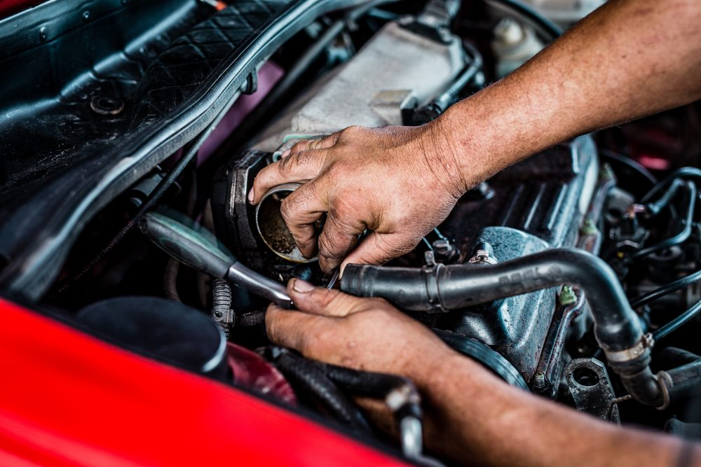 South Afircan mechanic bust working with a racthed spanner inside of a car.