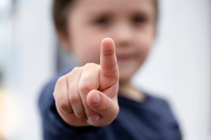 Blurry face of little boy finger pointing at camera, Selective focus of kid primary school boy pointing at you with his finger, Spoiled children concept