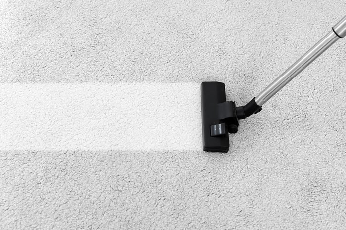 Removing dirt from soft carpet with vacuum cleaner indoors