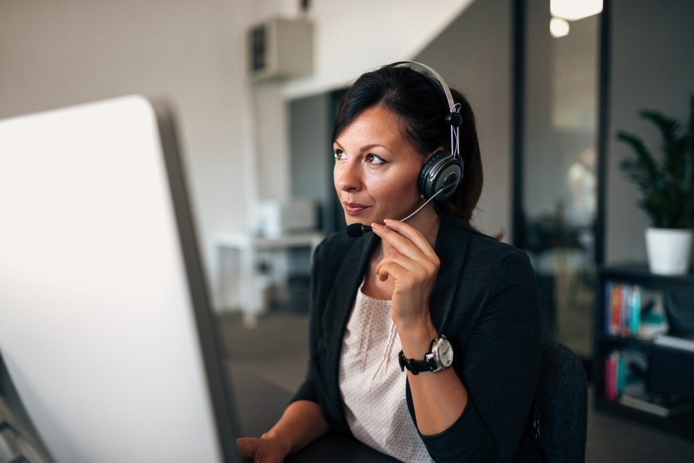 Close-up image of freelance operator talking with headsets and consulting.