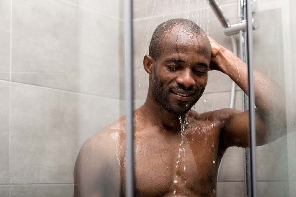 handsome smiling african american man with closed eyes taking shower