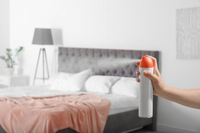Woman spraying air freshener in bedroom