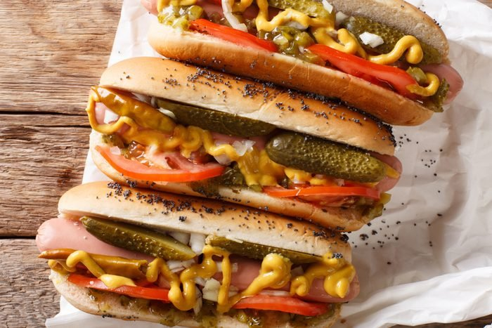 Homemade Chicago style hot dogs with mustard, tomatoes, pickled cucumbers, onions and relish close-up on the table. Horizontal top view from above
