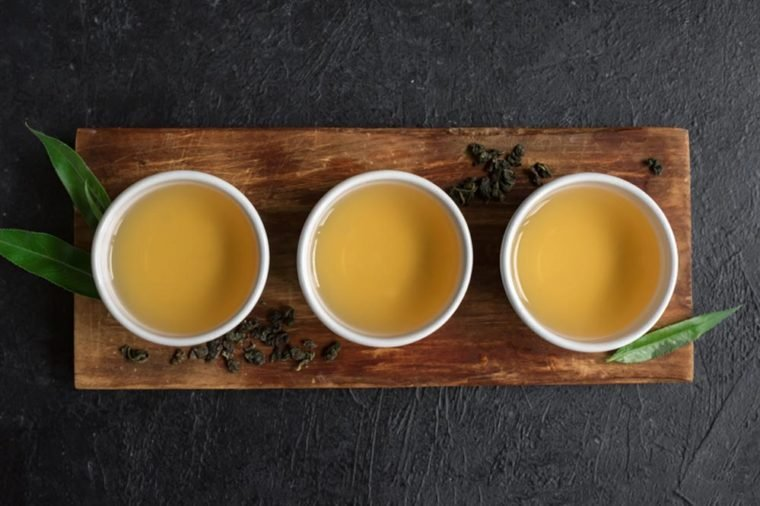 Green tea in ceramic cups, dry green oolong tea and tea leaves on black stone table, copy space.