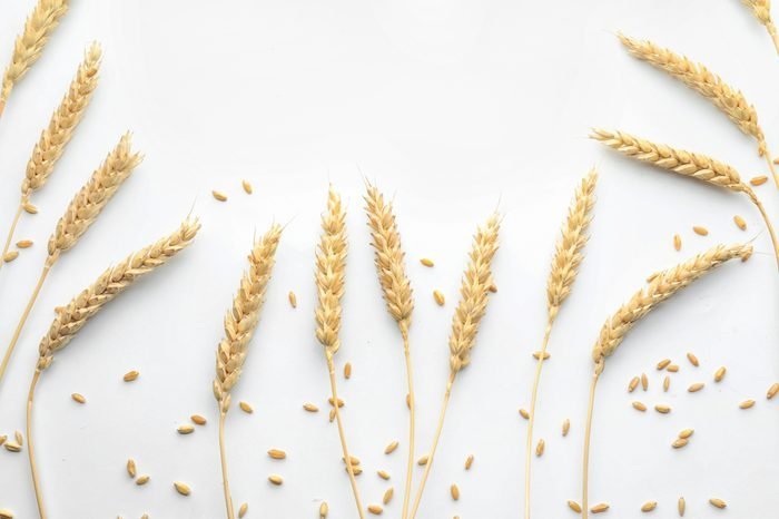 Wheat grains with spikelets on white background