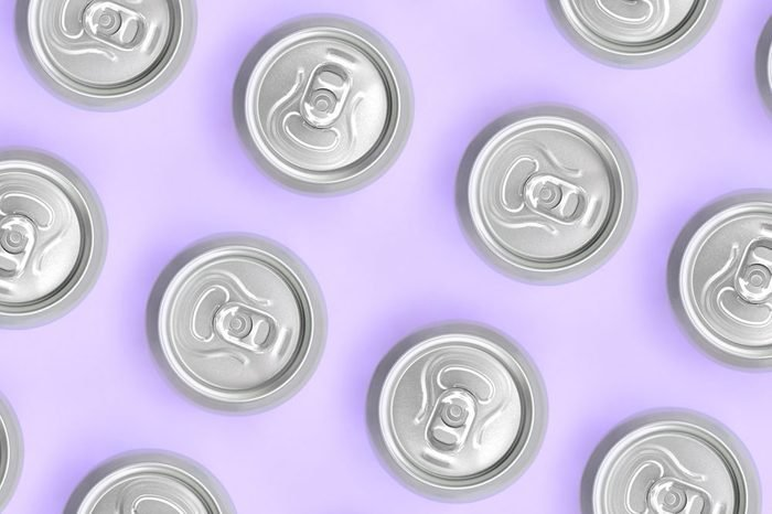 Many metallic beer cans on texture background of fashion pastel violet color paper in minimal concept