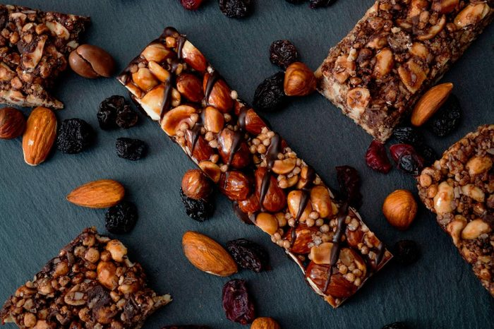 Healthy snacks, fitness lifestyle and high fiber diet concept with granola energy bars surrounded by dried fruits, hazelnuts and almonds on a black stone with dramatic light