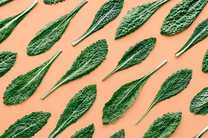 Fresh organic green kale leaves pattern on a pastel peach background, flat lay healthy nutrition concept