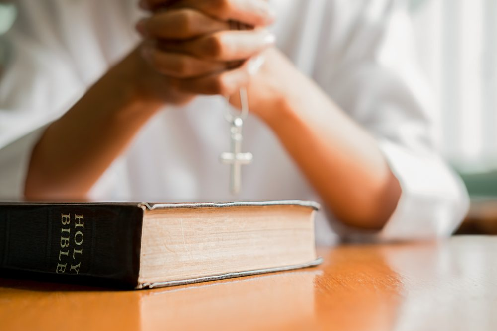 Christian woman praying on holy bible. Hands folded in prayer a holy bible in church concept