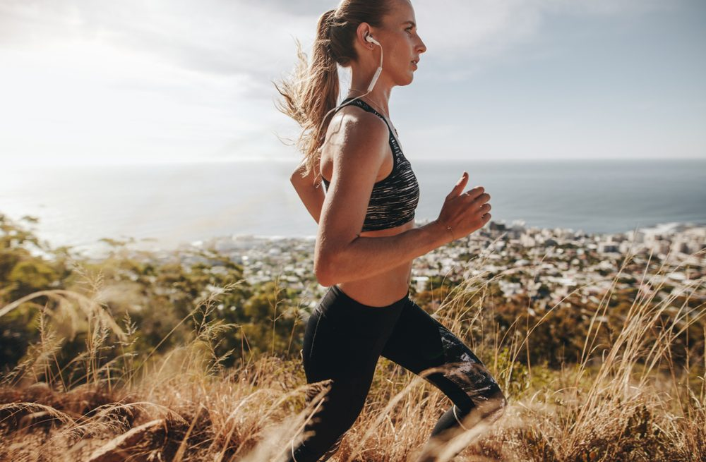 Side view of fit young woman wearing earphones running through mountain trail. Female runner training over rough trail in hillside.