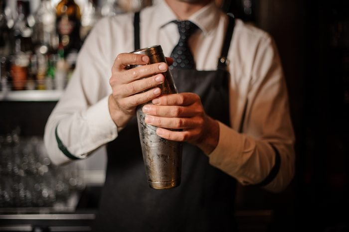 Professional male bartender holding a steel shaker ready to prepare a fresh cocktail at the bar counter