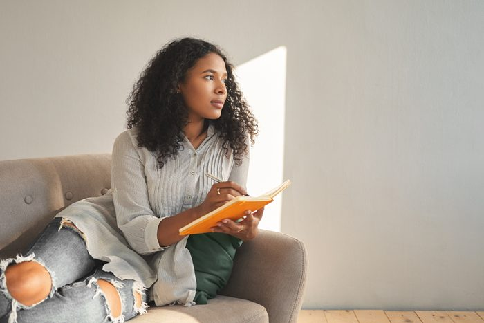 Attractive young dark skinned female with Afro hairstyle relaxing on couch at home, having pensive thoughtful look, writing down ideas for her own startup project, using pen and copybook