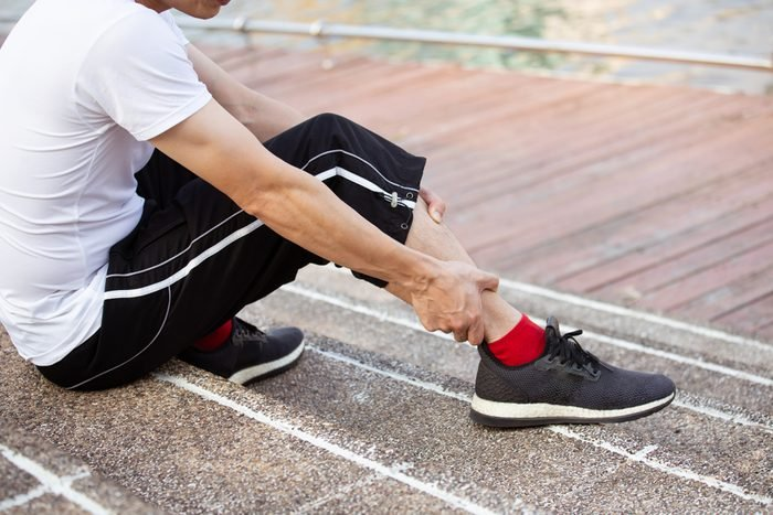 sport man feeling leg pain, ankle pain or sore which sitting up on the step healthy concept.