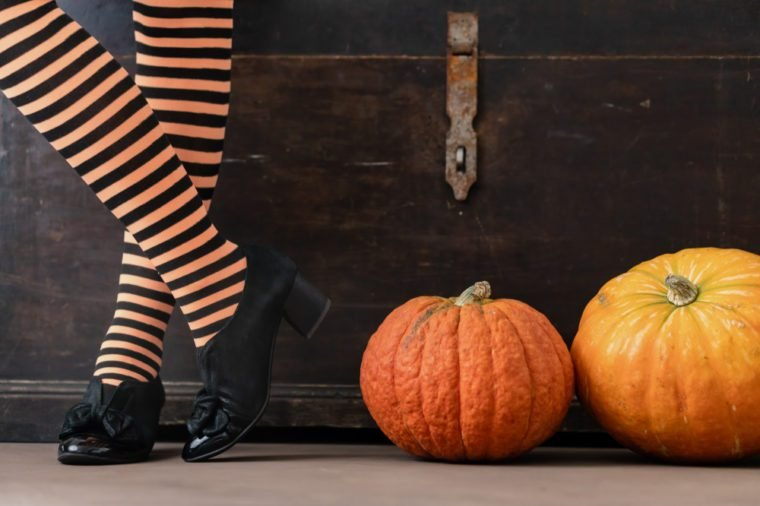 Happy halloween! Female feet in stockings with an orange pumpkin