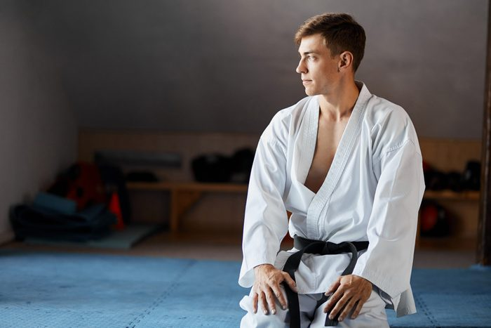 Karate do man in kimono sits on knees on floor in martial arts gym