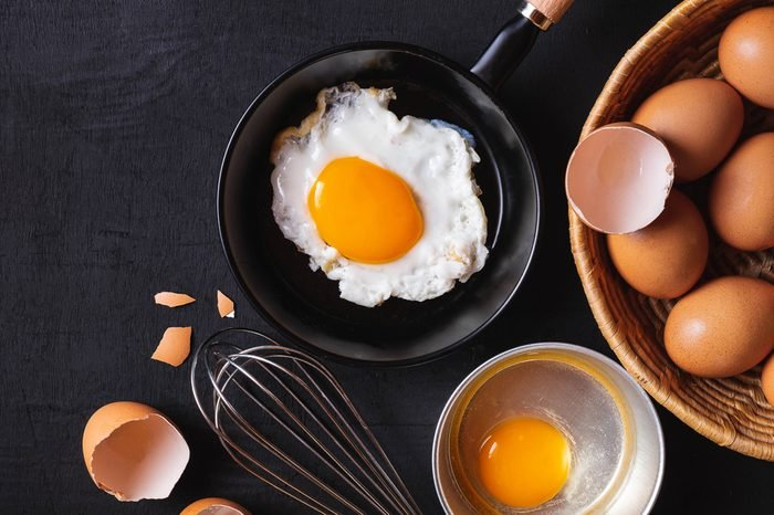 Frying pan in eggs and raw eggs