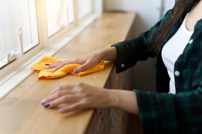 Housekeeping woman is cleaning wooden counter next to window, removing dust by wiping the orange rag. Happy cleaning concept.