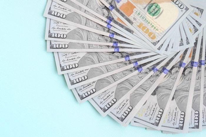 Fan of a US dollar bills of a new design lies on a light blue background