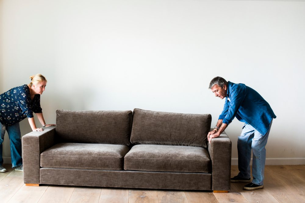 Couple moving a brown couch
