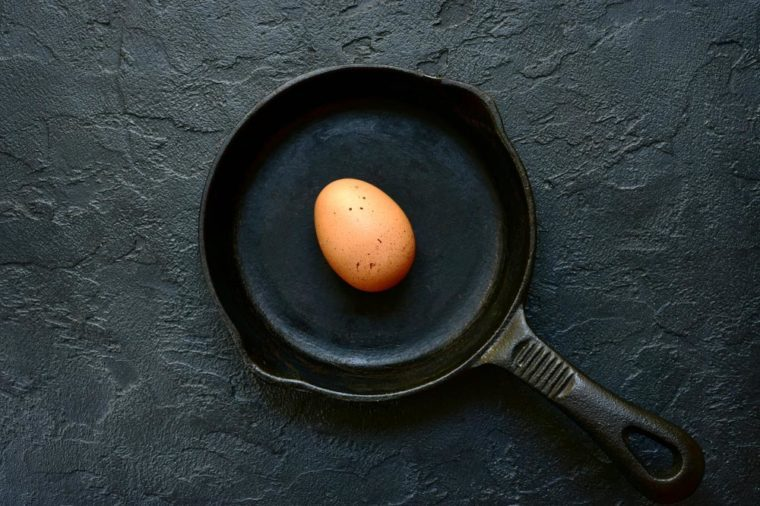 Fresh uncooked egg on a cast iron pan over black slate, stone or concrete background.Top view with copy space.