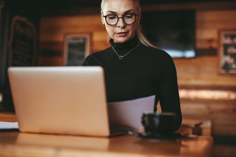 Senior businesswoman reading some documents at coffee shop. Female in casuals sitting at cafe table with laptop reading business report.