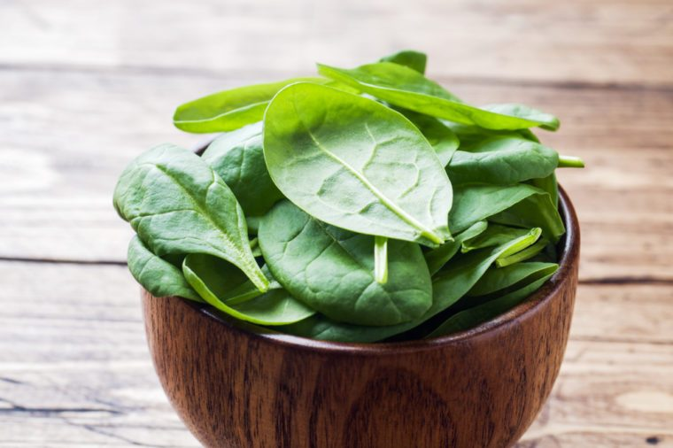 Fresh spinach leaves in bowl on rustic wooden table