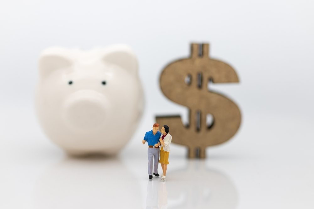 Miniature people : Couple standing area front of piggy bank and wooden dollar. Image use for Valentine's day , planning life after marriage concept.
