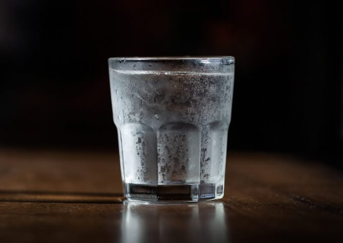 Cold water in a glass with ice on a wooden table by the window. Used for drinking to keep the body fresh. water cup dark tone