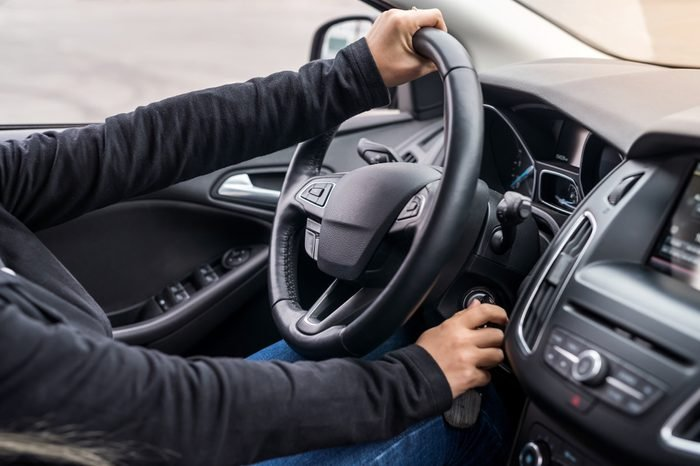Female hands on steering wheel starting a car