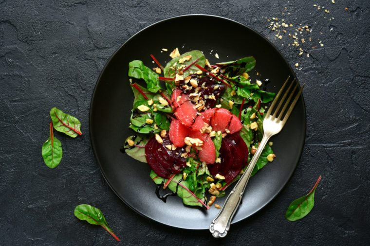 Delicious salad with chard leaves, beetroot and grapefruit slices on a black plate over dark slate, concrete or stone background.Top view.
