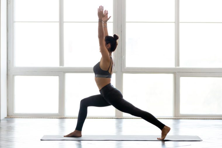 Young sporty woman practicing yoga doing Warrior one exercise, Virabhadrasana 1 pose, working out wearing sportswear pants, bra, at indoor yoga studio, full length side view, white window background