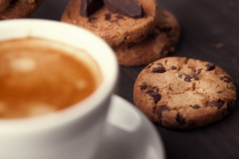 Homemade chocolate chip cookies and a cup of coffee on dark old wooden table. Sweet dessert.