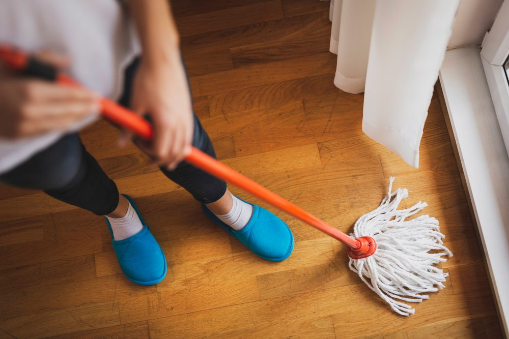 High angle view of woman holding a floor wiper and wiping floor, keeping the daily home hygiene. Focus on the mop