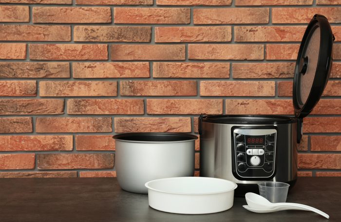 Modern electric multi cooker, parts and accessories on table near brick wall. Space for text