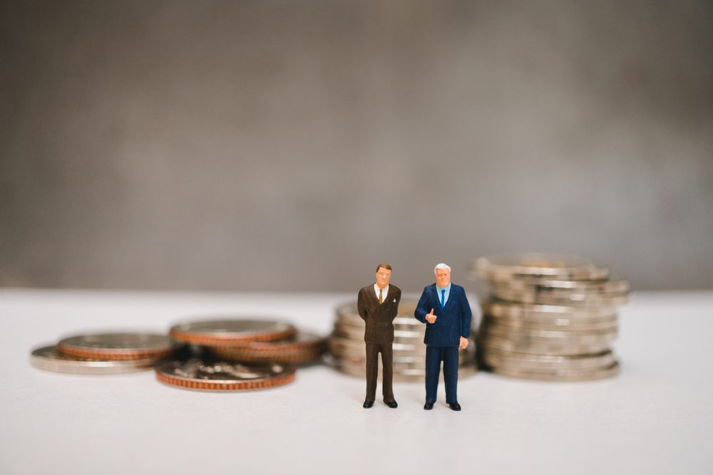 Miniature people, couple businessman standing on pile coins background using as business corporation and financial concept