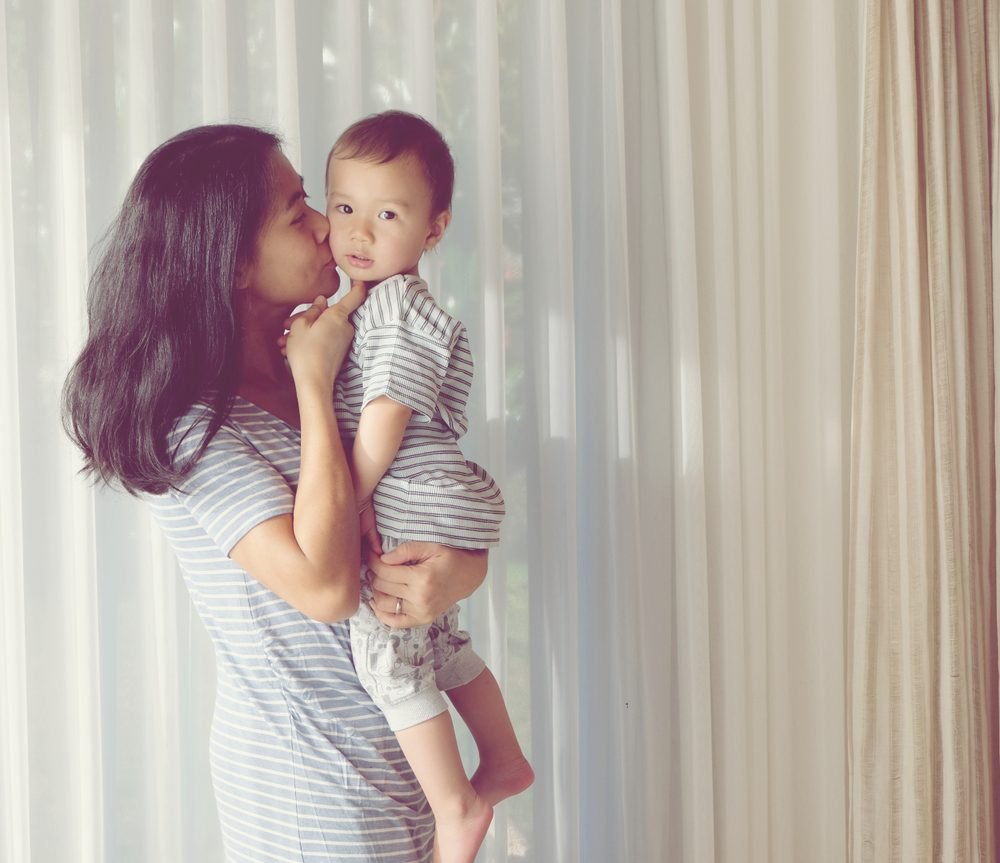 Young Asian mother is kissing her lovely one year old son. Vintage photo mom and son