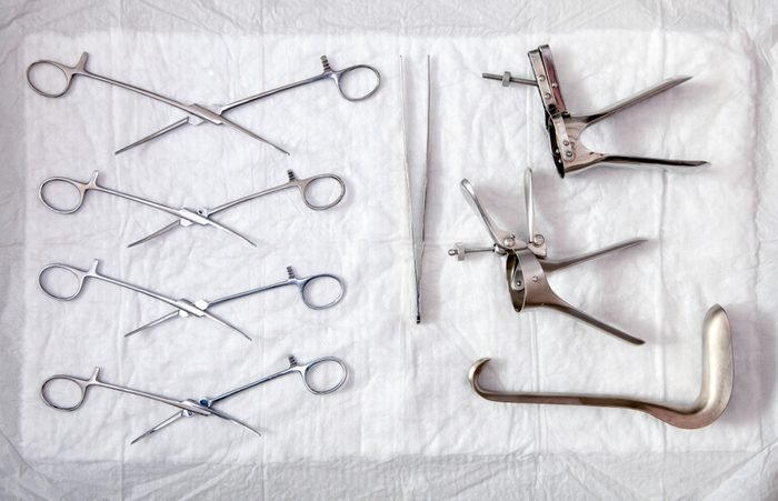 Gynecological sterile tools. A lot of instruments of gynecologist on white background. Top view.
