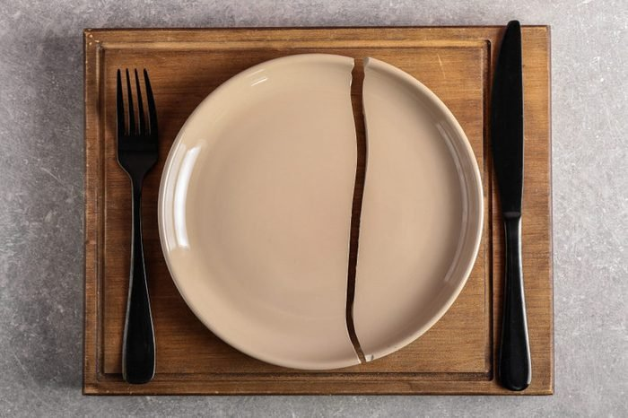 Cracked plate with cutlery and wooden board on grey background