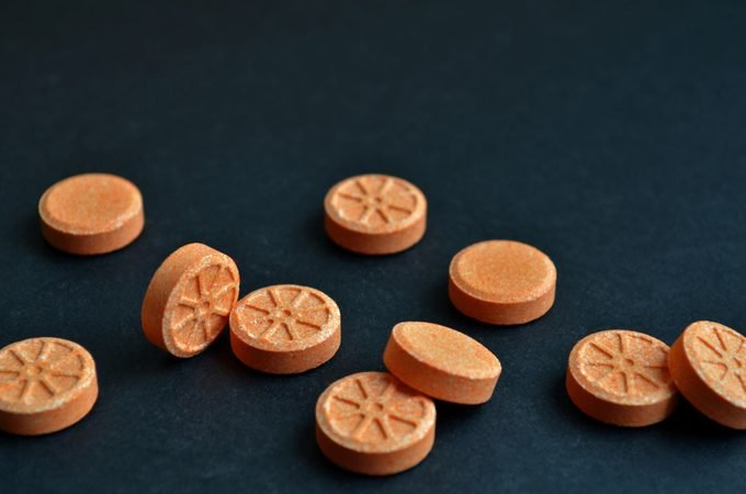 Orange round orange shaped tablets are scattered chaotically on black background with copyspace