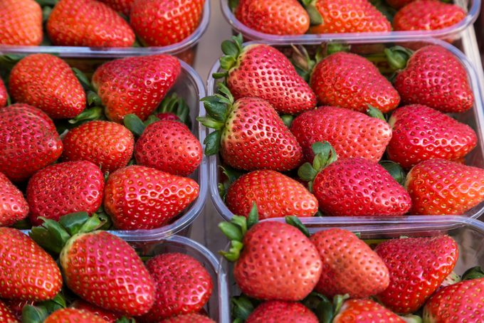 Strawberries in plastic baskets at the market with a soft focus field