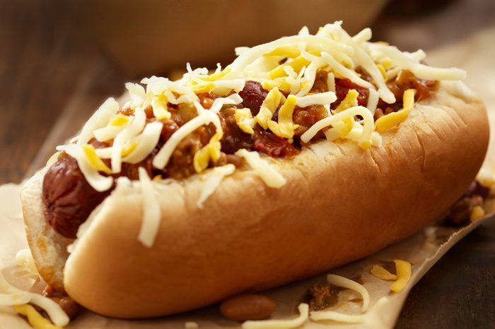 Homemade chili cheese hot dog with melted cheddar and monterey jack cheese and chili con carne sauce on a steamed bun.