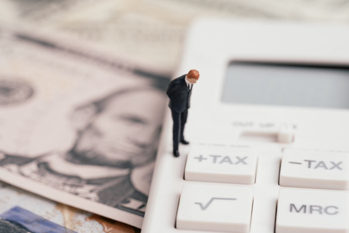 Tax calculation or tax refund for individual or company concept, miniature businessman leader standing and thinking with tax plus button on calculator and pile of US America Dollar banknotes money.