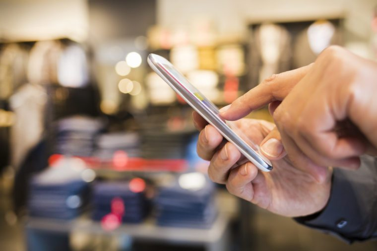Close up of a man using Smart-Phone in clothing store