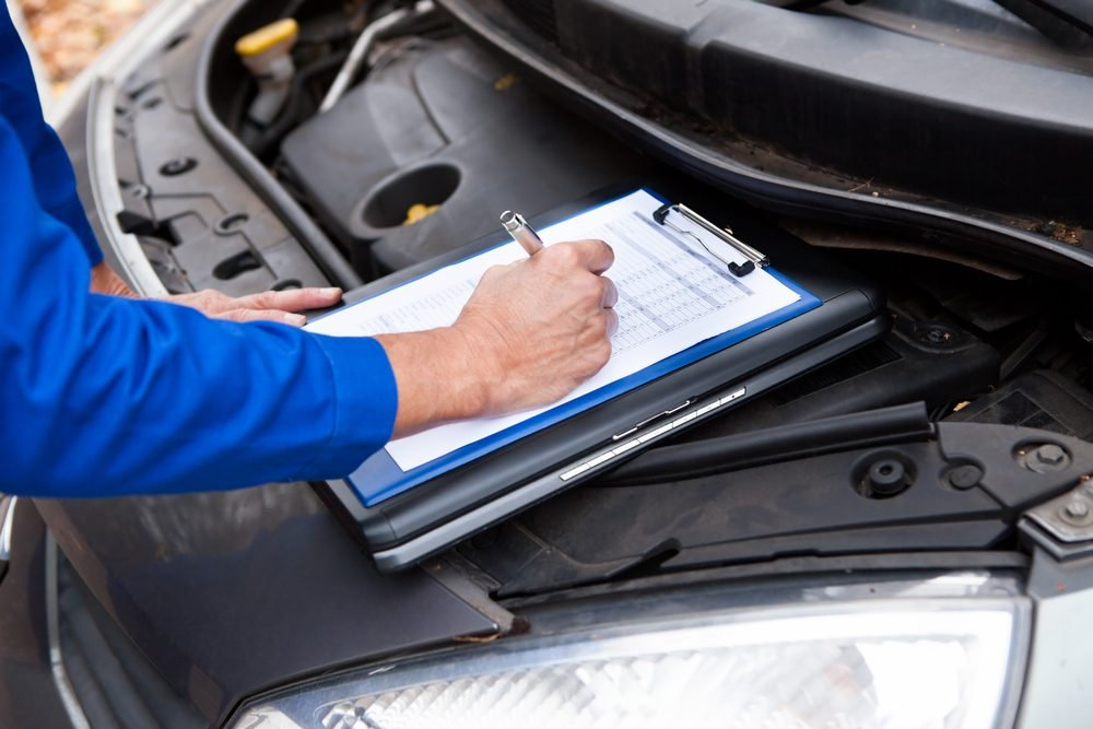 Close-up Of A Mature Mechanic Maintaining Car Records