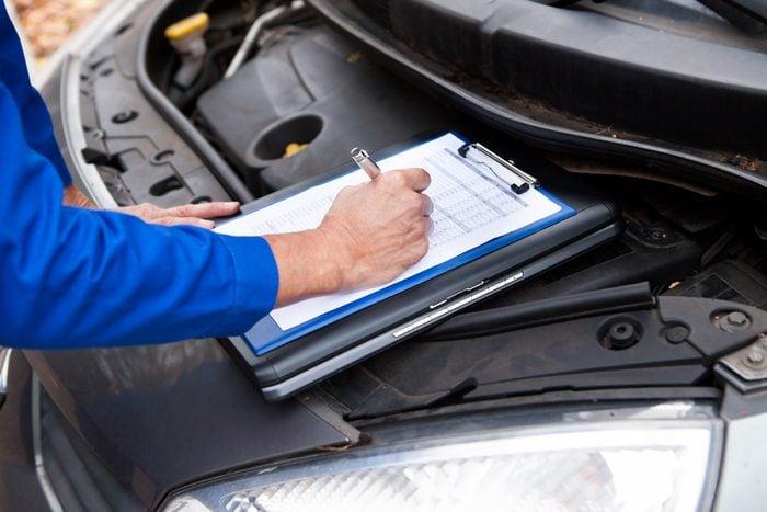 Close-up Of A Mature Mechanic Maintaining Car Records