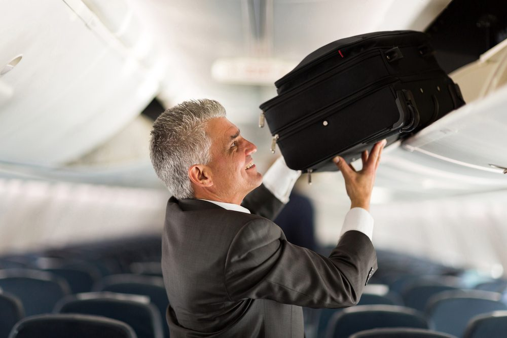 mature businessman putting luggage into overhead locker on airplane