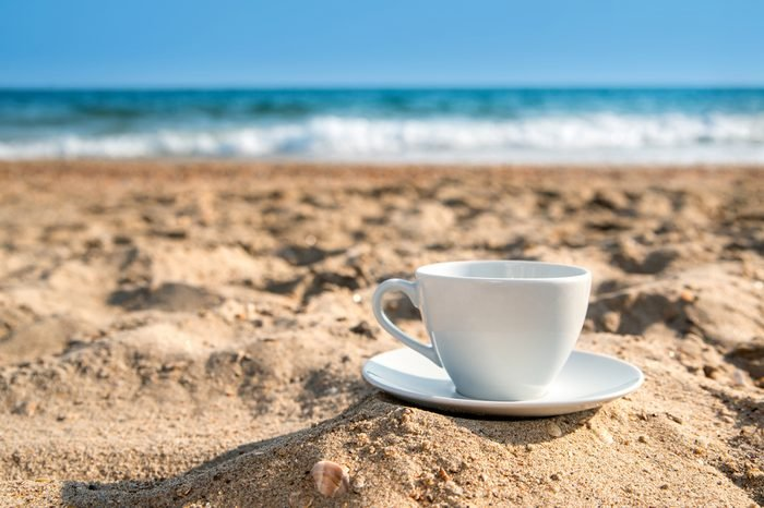 white cup with tea or coffee on sand beach front of sea, close up