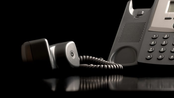Telephone handset off the hook lying on a black reflective surface alongside the instrument , close up low angle view with copyspace.