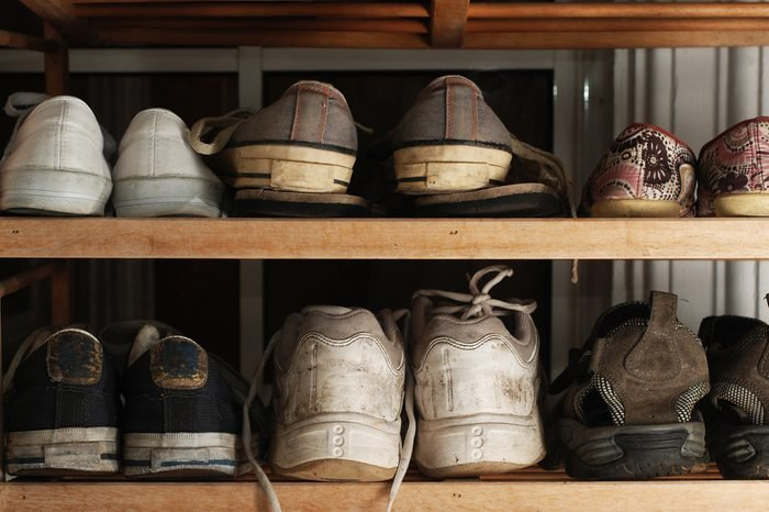 Several old and worn shoes on shoe rack