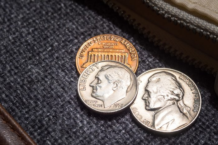 US dollar coins placed outside the wallet.